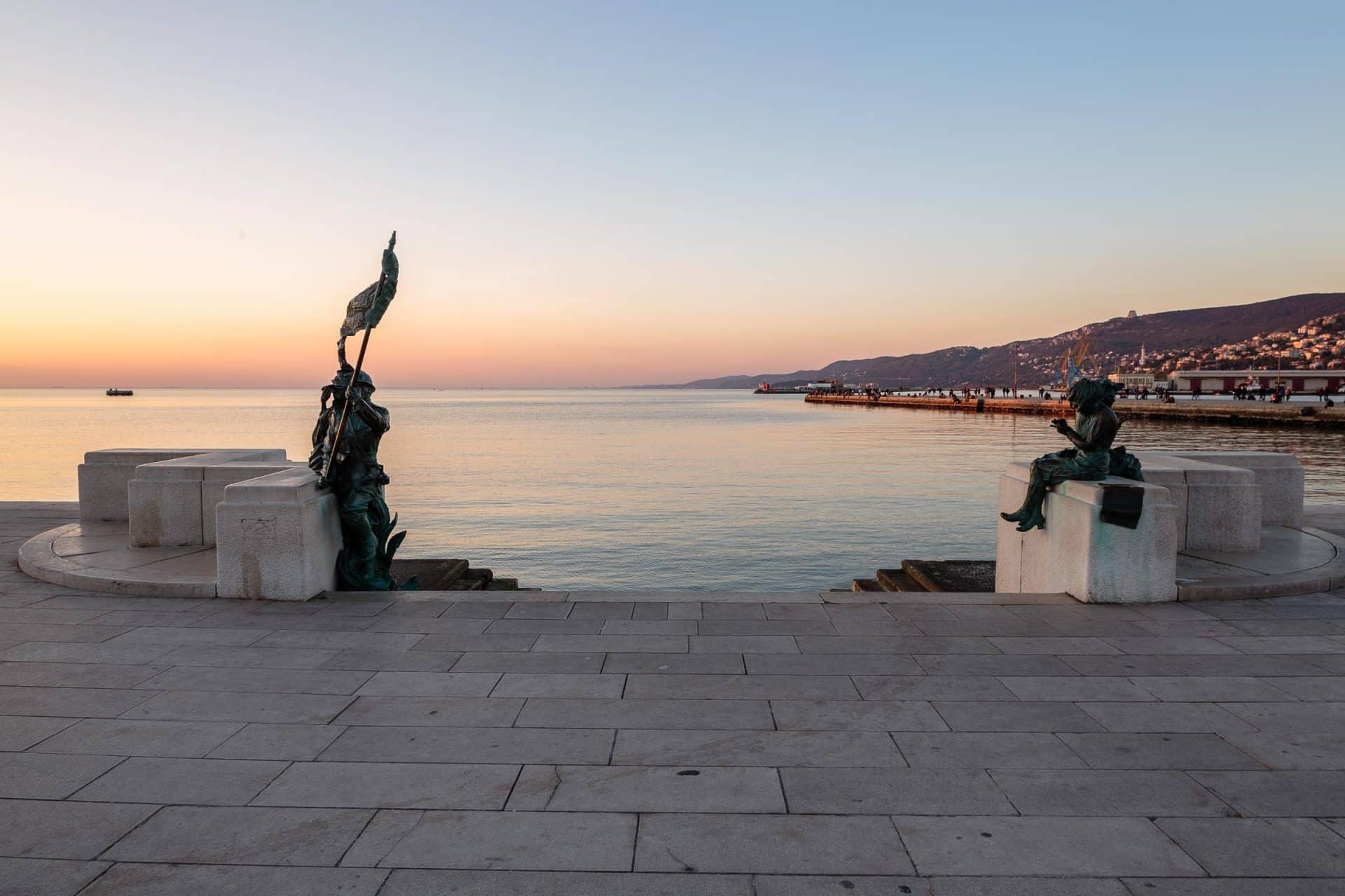 Statue sul mare di fronte a piazza unità